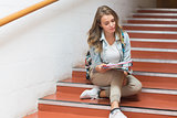 Pretty student sitting on stairs looking at camera