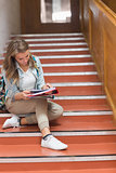 Pretty young student sitting on stairs looking at camera