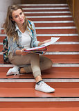 Happy young student sitting on stairs looking at camera