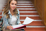 Smiling young student sitting on stairs looking at camera