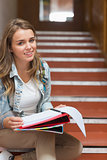 Cheerful young student sitting on stairs looking at camera