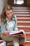 Cheerful young student sitting on stairs reading notes