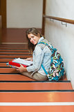 Cheerful young student sitting on stairs looking up at camera