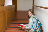 Happy young student sitting on stairs looking up at camera