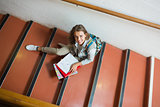 Smiling young student sitting on stairs looking up at camera
