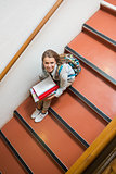 Young student sitting on stairs smiling up at camera