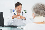Smiling doctor listening to senior patient at medical office