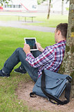 Student using his tablet pc outside leaning on tree