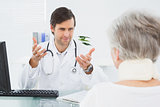 Doctor listening to senior patient at medical office