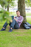 Smiling student using his tablet pc outside leaning on tree