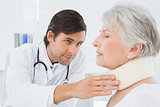 Doctor examining a senior patient's neck