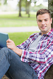 Cheerful student using his tablet pc outside leaning on tree