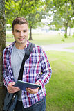 Handsome student leaning on tree looking at camera holding tablet