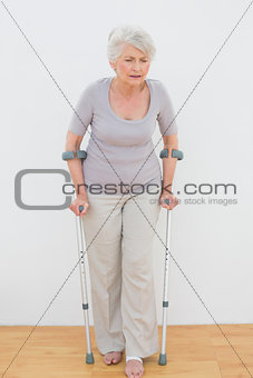 Full length of a senior woman with crutches