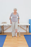 Senior woman with crutches in the hospital gym