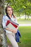 Happy student leaning on tree holding her books