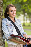 Cheerful young student leaning on tree holding her books