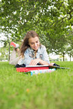 Smiling young student studying on the grass