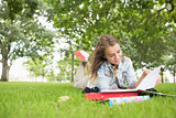 Happy young student studying on the grass