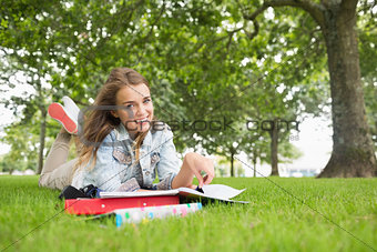 Happy young student lying on the grass studying