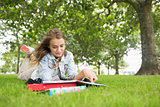 Happy student lying on the grass studying