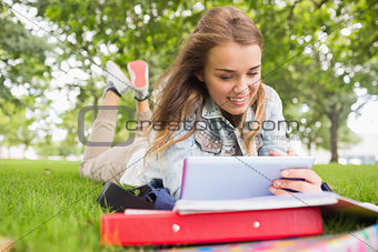 Happy student lying on the grass studying with her tablet pc