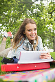 Cheerful student lying on the grass studying with her tablet pc
