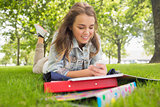 Pretty smiling student lying on the grass sending a text