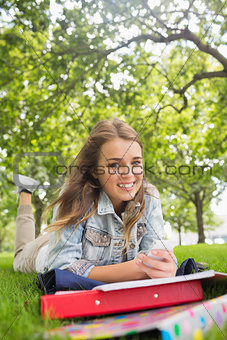 Young happy student lying on the grass sending a text