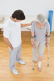 Male therapist assisting disabled senior patient to walk