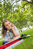Young happy student lying on the grass on the phone
