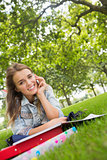 Young smiling student lying on the grass on the phone