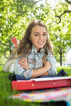 Young pretty student lying on the grass smiling at camera