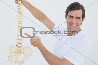 Portrait of a smiling male doctor with skeleton model