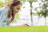 Happy student lying on the grass using her laptop