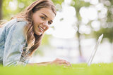 Happy student lying on the grass using her laptop looking at camera
