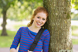 Happy redhead student leaning on tree looking at camera