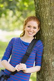 Pretty redhead student leaning on tree looking at camera
