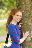 Smiling redhead student leaning on tree looking at camera