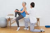 Male physiotherapist examining senior woman's back