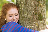 Smiling redhead hugging a tree