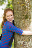 Laughing redhead hugging a tree