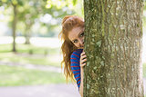 Cute redhead hiding behind a tree