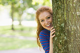 Smiling redhead hiding behind a tree