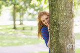 Smiling pretty redhead hiding behind a tree