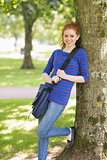 Happy redhead student leaning against a tree