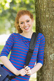 Cheerful student leaning against a tree