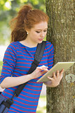 Cheerful student leaning against a tree using her tablet
