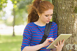 Redhead student leaning against a tree using her tablet