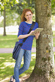 Smiling student leaning against a tree using her tablet pc